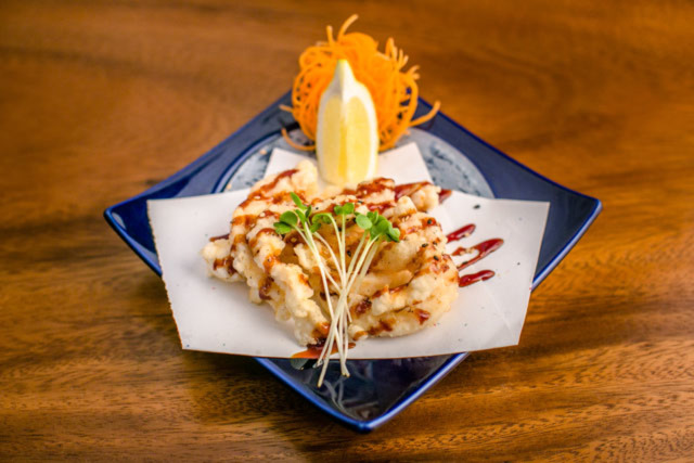 CRISP AND CRUNCH: Fried calamari drizzled with ponzu sauce and garnished with lemon, carrots, and sprouts Photo by Eric Meadows